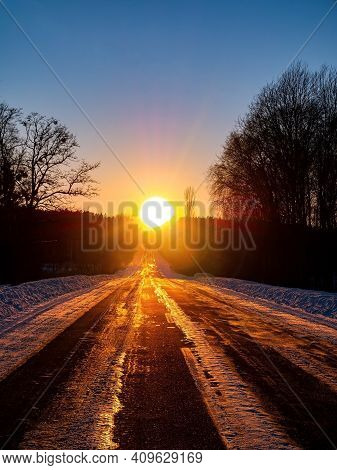 Winter Motor Road In The Snow Against The Backdrop Of A Sunny Sunset. Direction Of Movement. Automob