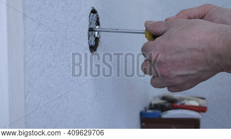 Side View Of An Electrician Working In An Open Hole Of The Socket Using A Screwdriver On A Blurred B