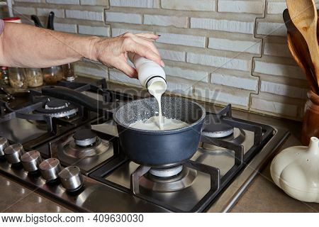 Cooking At Home In The Kitchen Using A Recipe From The Internet. Woman Pours Cream Into A Saucepan O