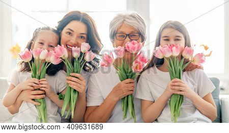 Happy women's day! Child daughters are congratulating mom and granny giving them flowers tulips. Grandma, mum and girls smiling and hugging. Family holiday and togetherness.