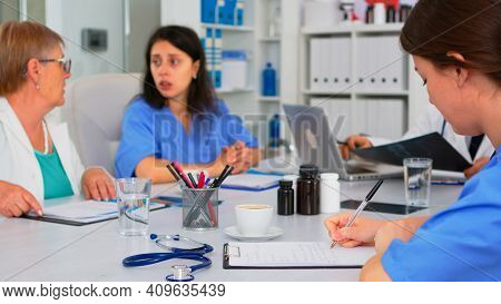 Nurse Writing On Clipboard While Profesional Teamworkers Having Medical Meeting Discussing In Backgr