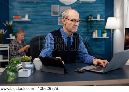 Senior Manager Working On Presentation Using Laptop And Tablet Pc Sitting At Office. Elderly Man Ent