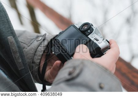 Close-up Of A Man Using A Camera. Photographer Outside In Winter. Selective Focus