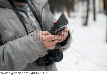 Photographer Uses Mobile Phone Outside In Winter. Man In A Jacket And With A Camera, Close-up. Selec