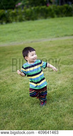 Little Child Playing In The Park. Portrait Of  Little Kid Running In The Playground With Smiling Fac