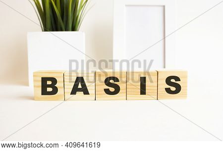 Wooden Cubes With Letters On A White Table. The Word Is Basis. White Background With Photo Frame, Ho