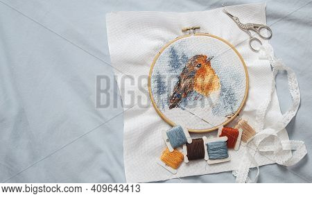 The Process Of Cross Stitching A Multicolored Bird On A White Canvas In A Wooden Hoop, A Floss Threa