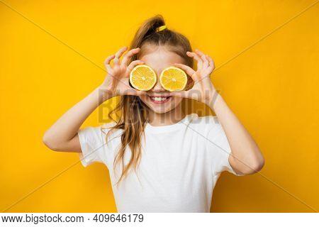 Little Smiling Cute Blond Girl In Yellow T-shirt Holding Halves Of Fresh Sour Lemon Fruit Near Eyes