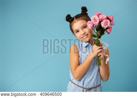 Adorable Smiling Little Girl Holding Bouquet Of Pink Roses On Blue Background. Copy Space For Text.
