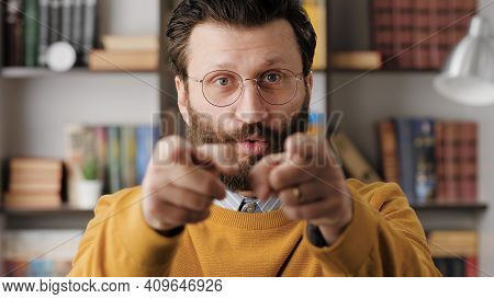 Man Points His Finger To You. Serious Frowning Bearded Man With Glasses In Office Or Apartment Room