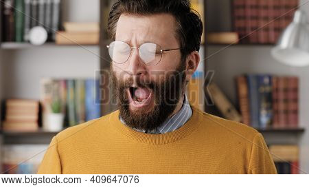 Man Yawns. Tired Sad Bearded Man In Glasses In Office Or Apartment Room Yawns, He Is Bored Or Wants