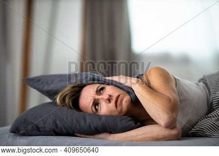 Sleepless lady covering ears with pillow. Noisy neighbors, tinnitus, insomnia or stress concept. Tired woman can't sleep. Awake in bed after coming home from her shift, work.