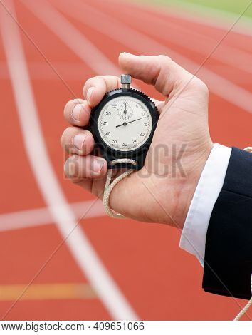 Time Is Running - Businessman In Stadium Holds Stopwatch In His Hand - Close-up