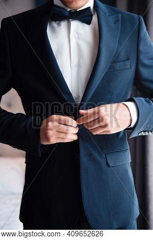 Stylish Groom Adjusting Black Suit During Morning Time