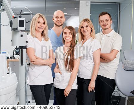 Dentists Looking At Camera And Smiling While Posing In Modern Dental Office. Women Expressing Positi