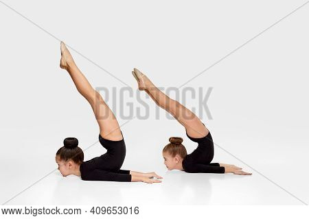 Two Flexible Gymnast Child Girl In Sportswear Performs Gymnastic Exercises On White Studio Backgroun