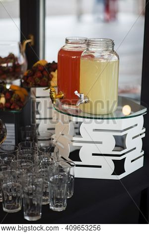 Refreshing Drinks In Glass Banks Standing On Buffet Table
