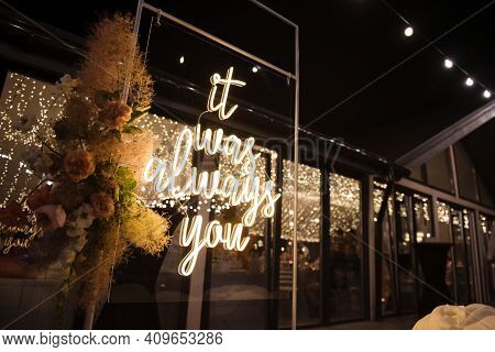 Wedding Stand Decorated With Flowers And Luminous Phrase