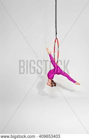 Little Child Girl Gymnast In Pink Sportwear Doing Twine On An Aerial Hoop
