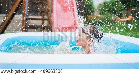 Staycation At Home. Little Girl In Swimsuit Rolls Down Slide Into Inflatable Rubber Pool. Swim Activ