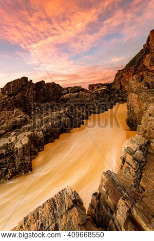 Water Rushes Up A Steeply Sloping Rocky Embankment On The Beach
