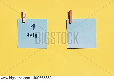 July 1st. Day Of 1 Month, Calendar Date. Two Blue Sheets For Writing On A Yellow Background. Top Vie