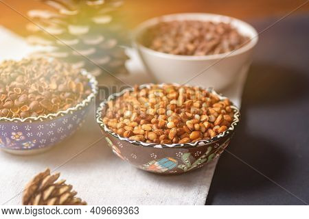 Still Life From Bowls With Peeled Pine Siberian Nuts, Shell Skins And Whole Nuts. On A Layer With A