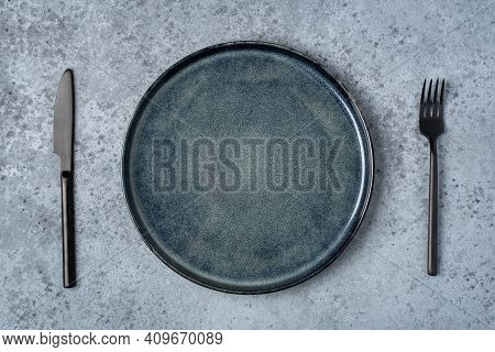An Empty Plate And Cutlery On A Gray Table. Top View.