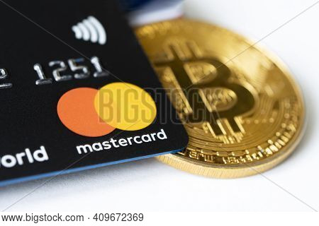 Gold Bitcoin Symbol And Credit Card Master Cards On The Table. February 20, 2021, Barnaul, Russia