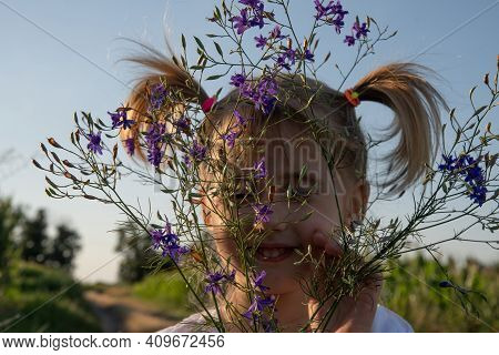 Kids Being Kids Concept. Little Girl Hiding Behind Bunch Of Wildflowers In Her Hands. Smiling Toddle