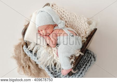 Newborn baby boy wearing a knitted soft blue jumpsuit and hat sleeping on a small wooden crib on soft knitted blankets
