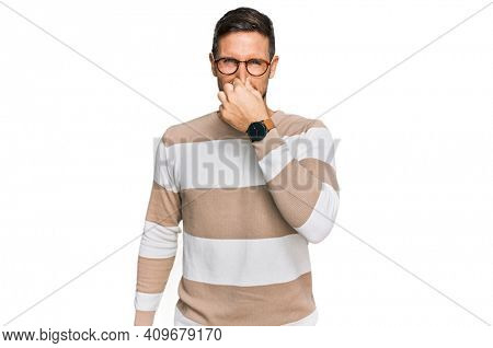 Handsome man with beard wearing casual clothes and glasses smelling something stinky and disgusting, intolerable smell, holding breath with fingers on nose. bad smell
