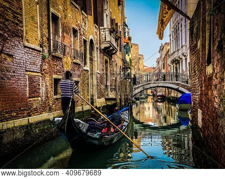 Gondolier seen from behind, driving a gondola with a family of tourists
