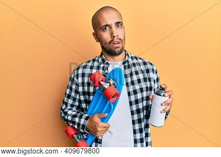 Hispanic adult skater man holding skate and graffiti spray in shock face, looking skeptical and sarcastic, surprised with open mouth