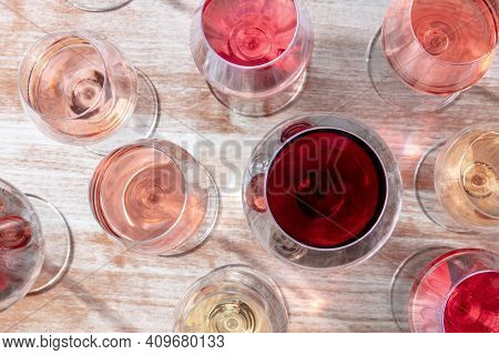 Wine Variety. White, Rose, And Red Wine In Many Glasses, Overhead Flat Lay Shot On A Wooden Backgrou