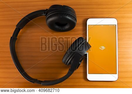 Spain, 02, 24, 2021. Mobile Phone With Audible Logo On Screen Close Up With Website On Laptop. Blurr