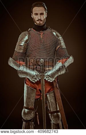 Brave medieval knight with sword and armour poses on a black background. Historical costumes and reconstruction.