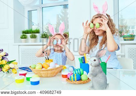 Happy mother with her daughter with bunny ears spend their leisure time preparing for Easter. Loving family concept. Easter holiday.