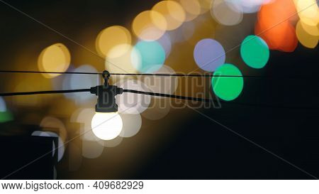 A Bright Light Bulb Shines With A Warm Light With A Black Wire Against The Backdrop Of A Beautiful,