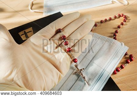 Gloves And A Mask Are Needed During The Coronavirus In Catholic Churches. The Bible And The Holy Ros