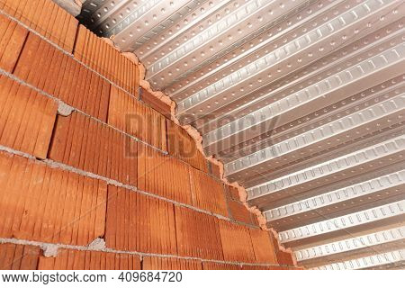 Roof Detail With Metal Decking Sheet And Brick Wall On Construction Site. Composite Decking For Roof