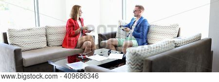 Young Man And Woman In Fashionable Clothes With Cups Of Tea In Hotel Room. Business Partners At Conf