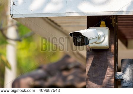 Online Security Cctv Camera Surveillance System Outdoor Of House. A Blurred Night City Scape Backgro
