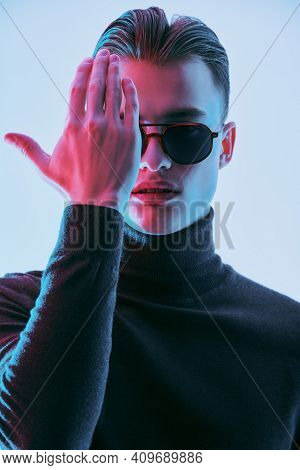 Handsome young man in modern sunglasses covers one eye with his hand. Men's accessories, optics. Studio portrait.