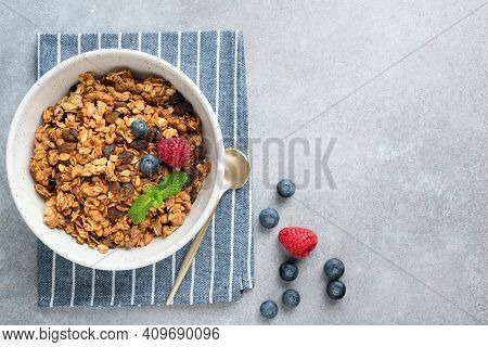 Bowl Of Crunchy Homemade Granola With Berries On Concrete Background, Top View, Copy Space