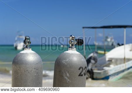 Close-up Of Scuba Diving Tanks On A Tropical Beach In Mexico. In The Background The Caribbean Sea, F