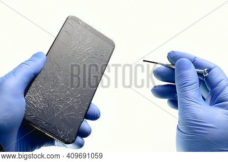 A Technician In Gloves Repairs A Broken Phone. The Master Is Holding A Smartphone With A Broken Disp