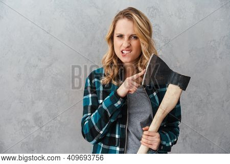Angry beautiful woman holding and pointing finger at hatchet isolated over gray wall