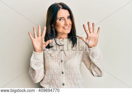 Middle age brunette woman wearing casual clothes showing and pointing up with fingers number ten while smiling confident and happy.