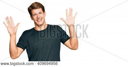 Handsome caucasian man wearing casual clothes showing and pointing up with fingers number ten while smiling confident and happy.